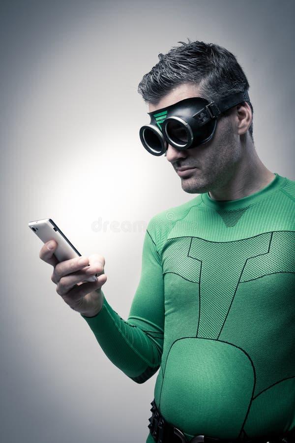 Supereroe che per mezzo di uno smartphone immagini stock