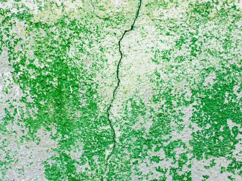Superfície abstrata rachada rachada no meio como a pintura verde que descasca fora de um fundo do muro de cimento Sujo velho, res imagens de stock