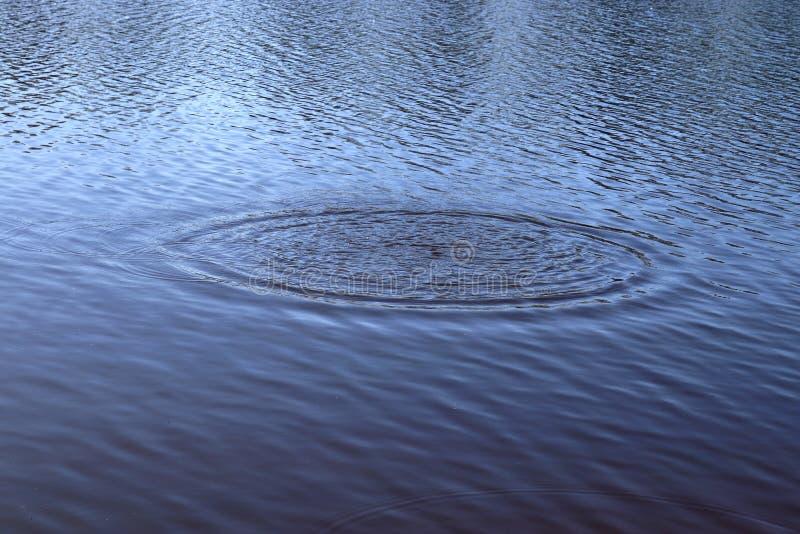 Superfície azul da água do lago com ondinhas e artigo do espirro que cai nele ao refletir a luz solar fotos de stock