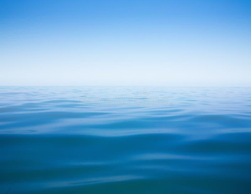 Superfície clara do céu e da água do mar calmo ou do oceano fotografia de stock