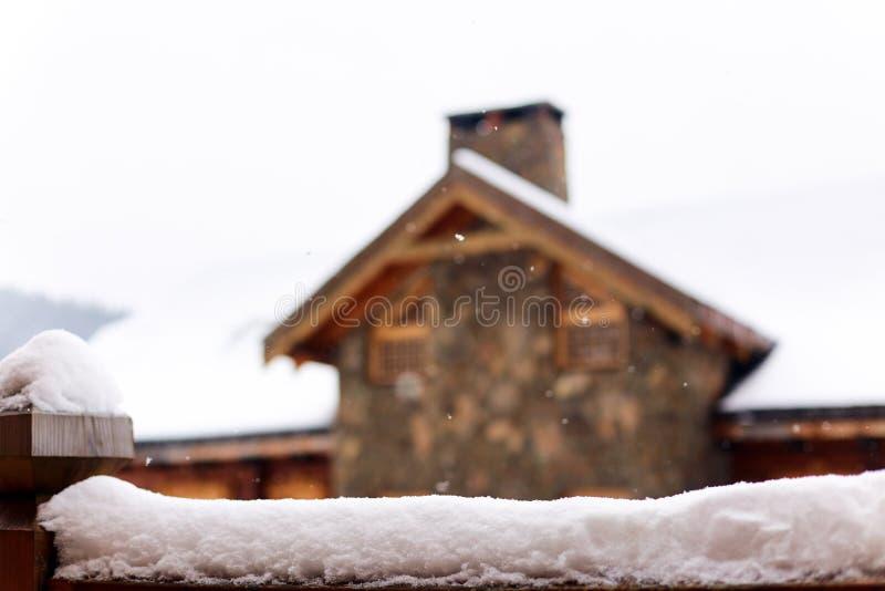 Superfície coberto de neve para a colocação do produto Casa borrada feita da madeira e da pedra no fundo Queda de neve no dia de  fotos de stock royalty free