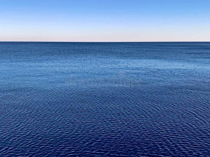Superfície da água de Minimalistic com horizonte azul do seascape e o céu claro do inclinação fotos de stock