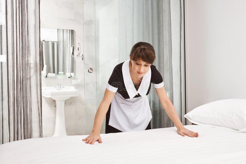 A superfície da cama deve ser limpa e arrumada Tiro interno do uniforme vestindo da empregada doméstica da mulher, fazendo a cama fotos de stock