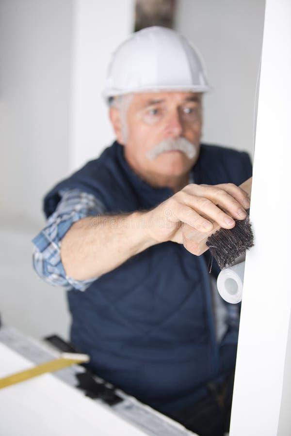 Superfície da parede da limpeza do trabalhador com cabo de vassoura foto de stock