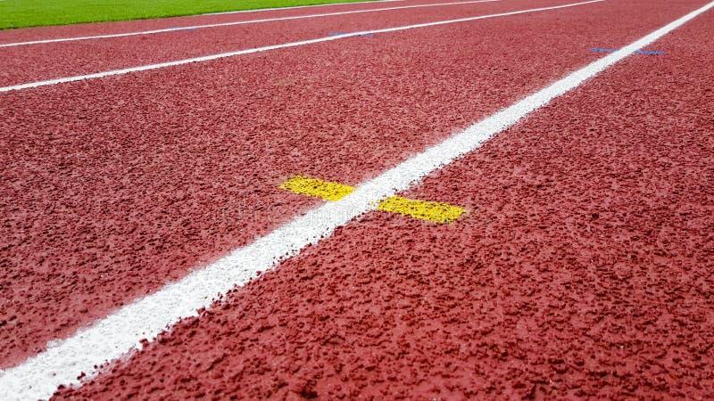 A superfície das pelotas de borracha da migalha no campo do atletismo da escada rolante fotografia de stock