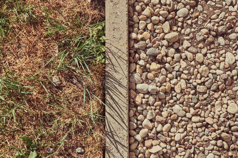 Superfície de estrada A pedra esmagada em um lado separou por uma beira com um gramado no outro lado fotografia de stock royalty free