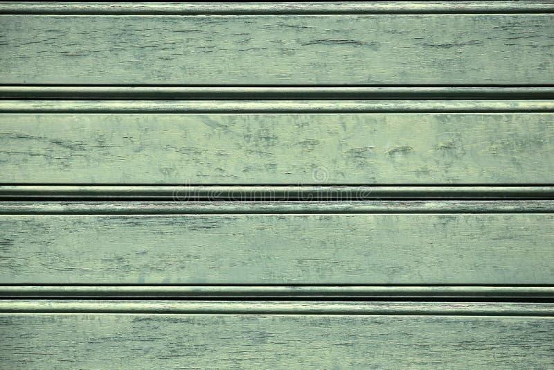Superfície de madeira velha das pranchas firmemente pregadas com quebras e pintura exfoliating Fundo verde fotografia de stock royalty free