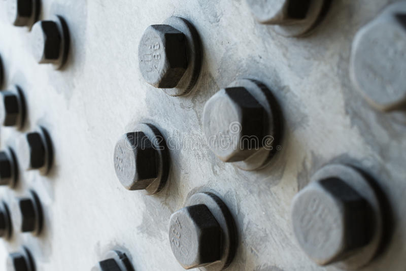 Superfície de metal cinzenta com cabeças de parafuso sextavadas imagens de stock royalty free