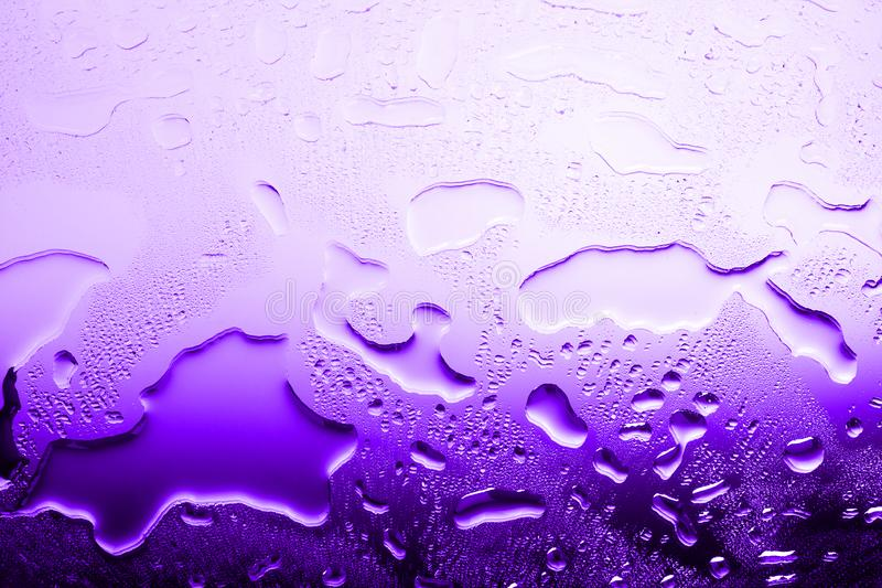 Superfície de vidro molhada nas gotas da água, inclinação violeta, textura da água derramada em cores roxas brilhantes, fundo abs imagens de stock royalty free