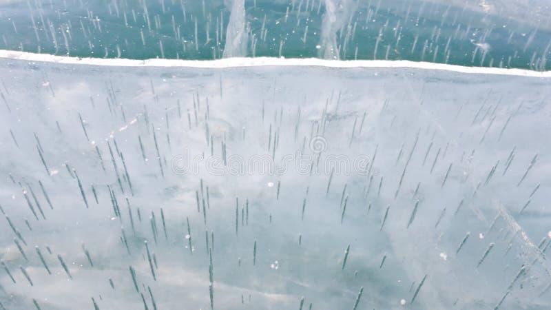 A superfície do gelo do mês do Lago Baikal na primavera As bolhas sob a forma das agulhas longas são visíveis sob o gelo fotografia de stock