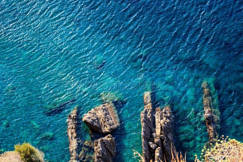 A superfície e as rochas do mar de turquesa aproximam Corniglia foto de stock