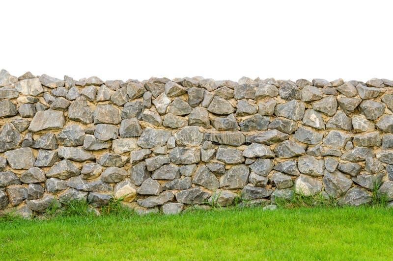 Superfície real da parede de pedra da cerca com cimento no campo de grama verde imagem de stock royalty free