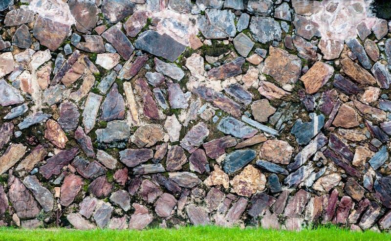 Superfície real rachada desigual decorativa da parede de pedra do teste padrão com cimento e grama verde fotos de stock