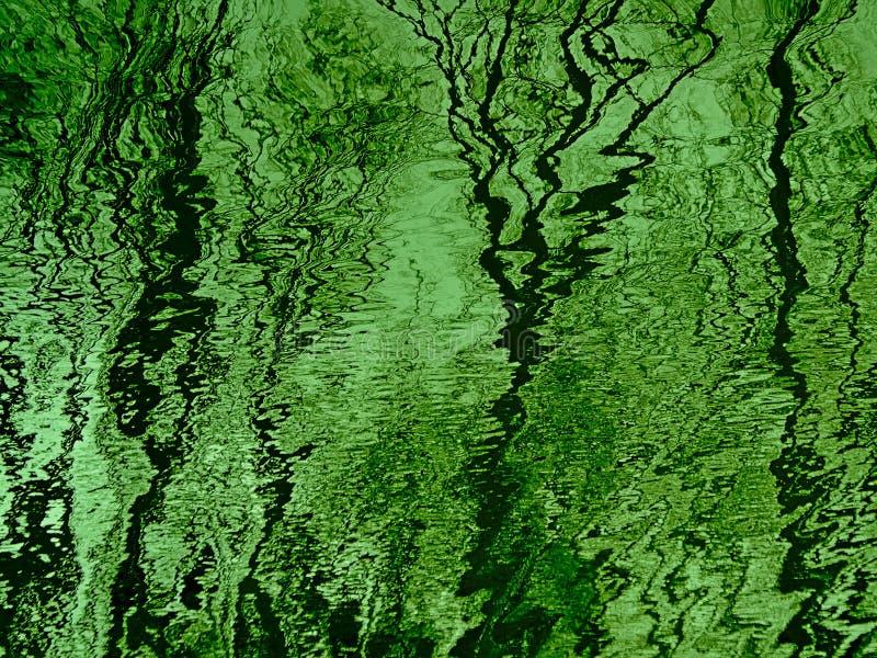 Superfície rippling verde da água com reflexões de árvores e do céu desencapados fotos de stock