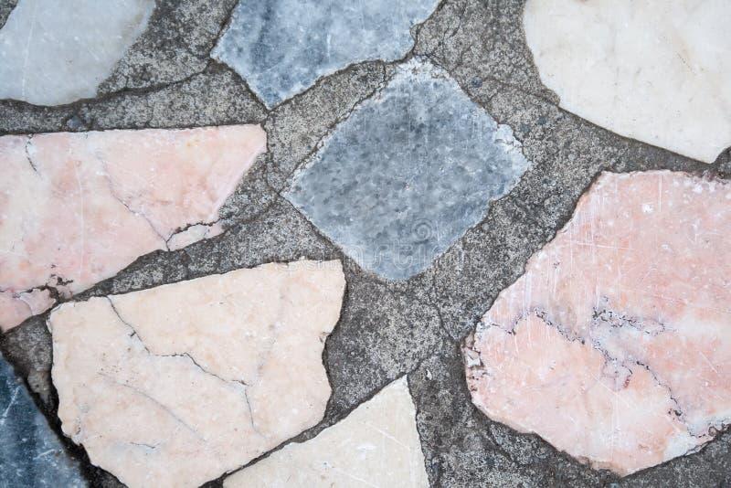 Superf?cie concreta com os remendos m?ltiplos de pedras coloridas closeup imagens de stock