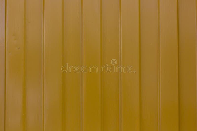 Superficie amarilla metálica con el fondo de la textura del modelo de las rayas verticales imagenes de archivo