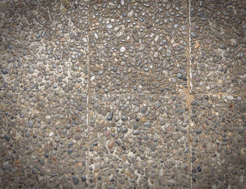 Superficie approssimativa di rivestimento aggregato esposto, di struttura pavimento lavato pietra a terra, fatto di piccola pietr fotografie stock