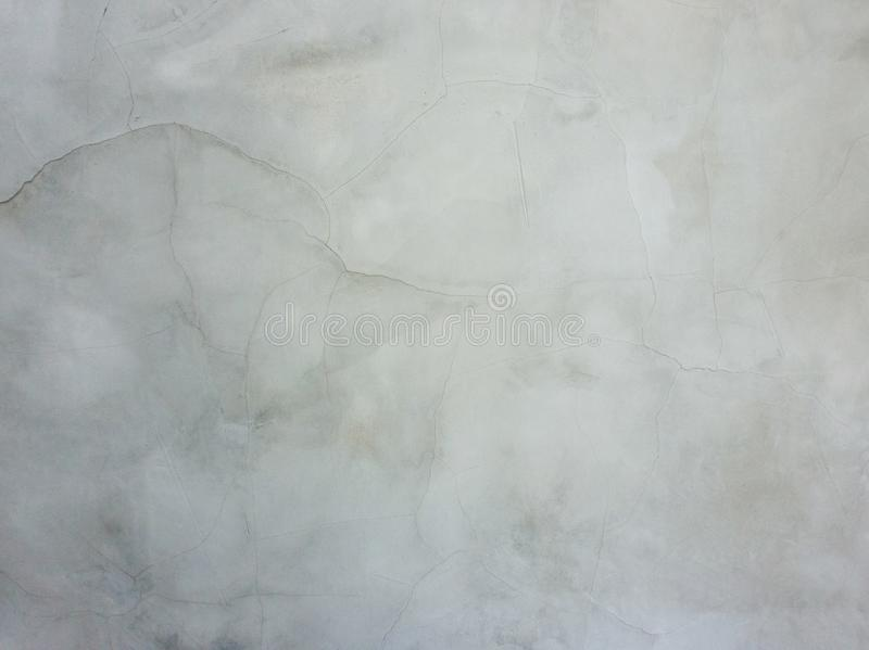 Superficie astratta fuori dalla parete liscia e grigia del gesso con le crepe e dai graffi Vecchia struttura grungy e stagionata  immagine stock libera da diritti
