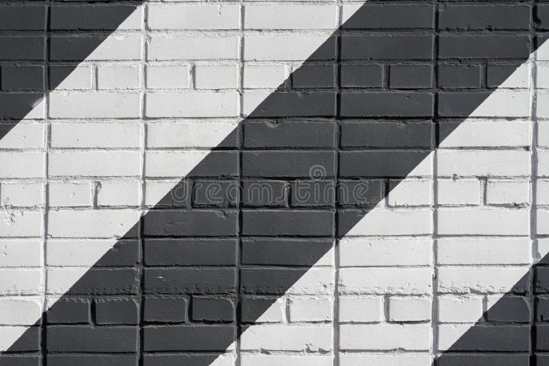 Superficie in bianco e nero diagonalmente dipinta dei mattoni di colore della parete, come graffiti Struttura grafica di lerciume immagine stock libera da diritti