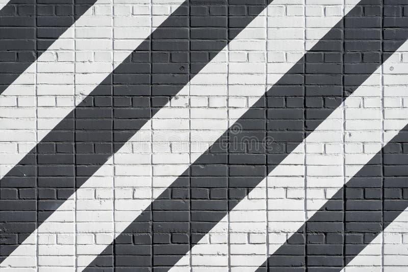 Superficie in bianco e nero diagonalmente dipinta dei mattoni di colore della parete, come graffiti Struttura grafica di lerciume fotografia stock