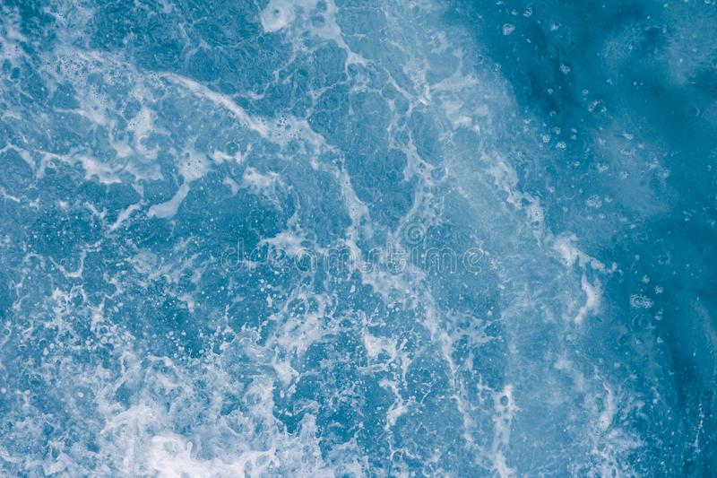Superficie blu-chiaro del mare con le onde, la spruzzata, la schiuma e le bolle ad alta marea ed a spuma, fondo astratto fotografia stock libera da diritti