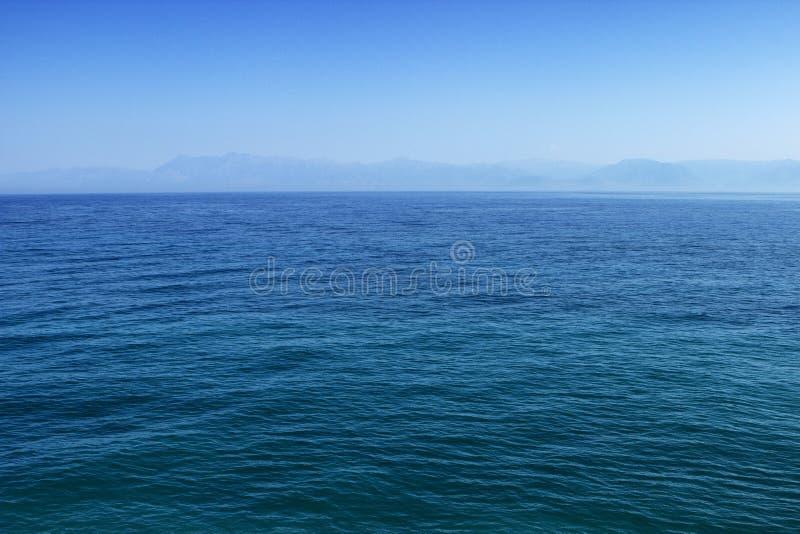 Superficie blu dell'acqua dell'oceano o del mare con l'orizzonte ed il cielo immagini stock
