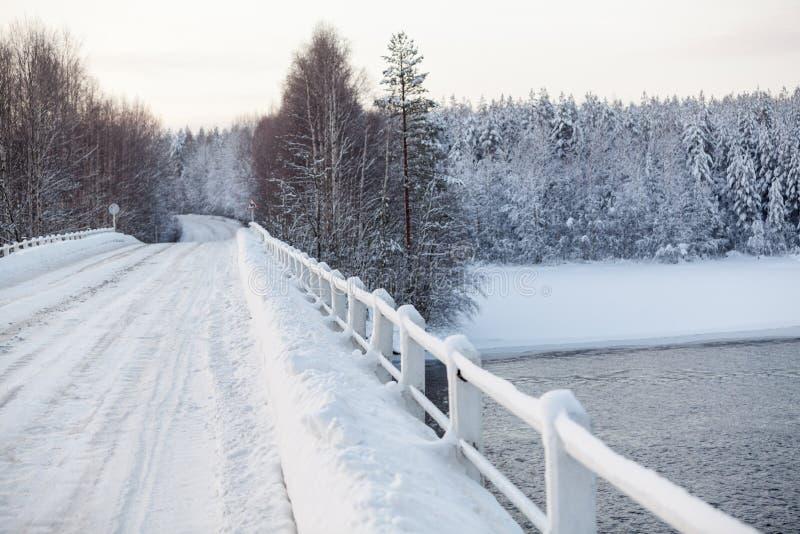 Superficie de la carretera nacional vacía en el puente a través de un río, estación Nevado del invierno fotos de archivo