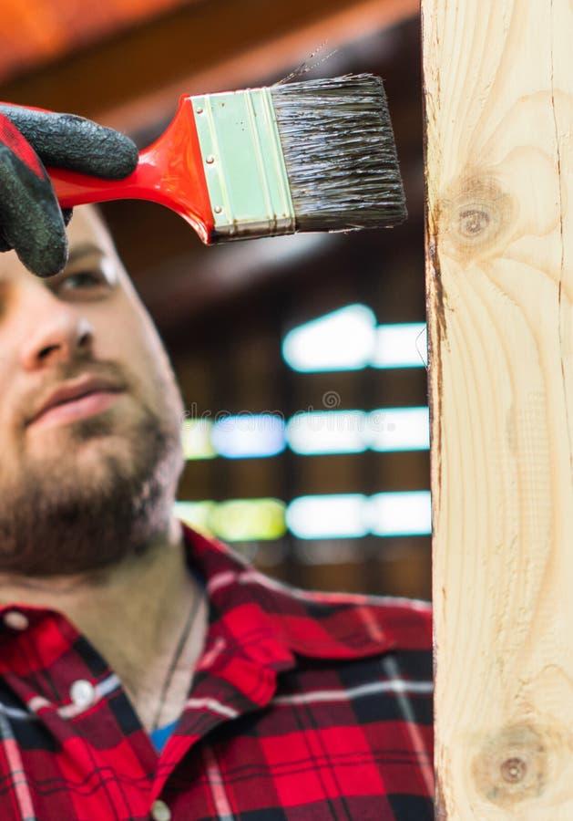Superficie de madera de la pintura del hombre joven con una brocha imagen de archivo libre de regalías