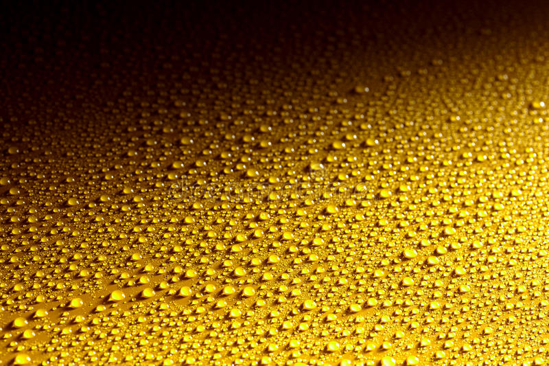 Superficie de metal amarillo mojada con descensos que relucir imagen de archivo