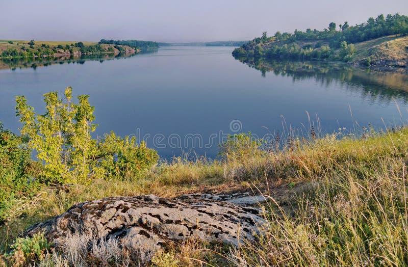 Superficie del río contra la perspectiva de costas rocosas con la hierba seca del verano y de arbustos verdes debajo del cielo gr foto de archivo libre de regalías
