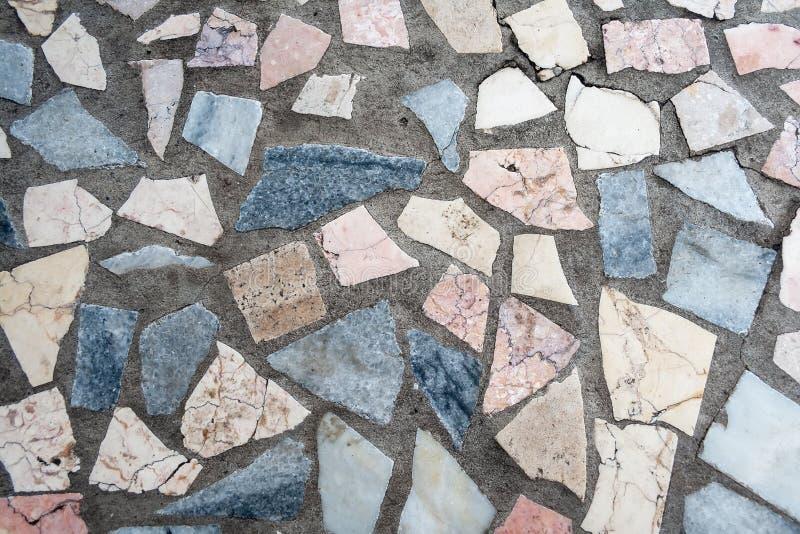 Superficie di calcestruzzo con le toppe multiple delle pietre colorate fotografie stock libere da diritti