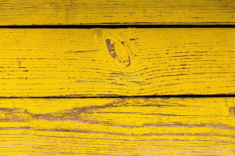 Superficie di legno con la pelatura della pittura gialla immagini stock