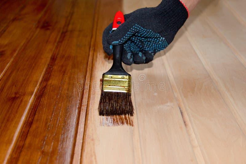 Superficie di legno della porta della pittura con una spazzola e pittura in guanti neri fotografia stock