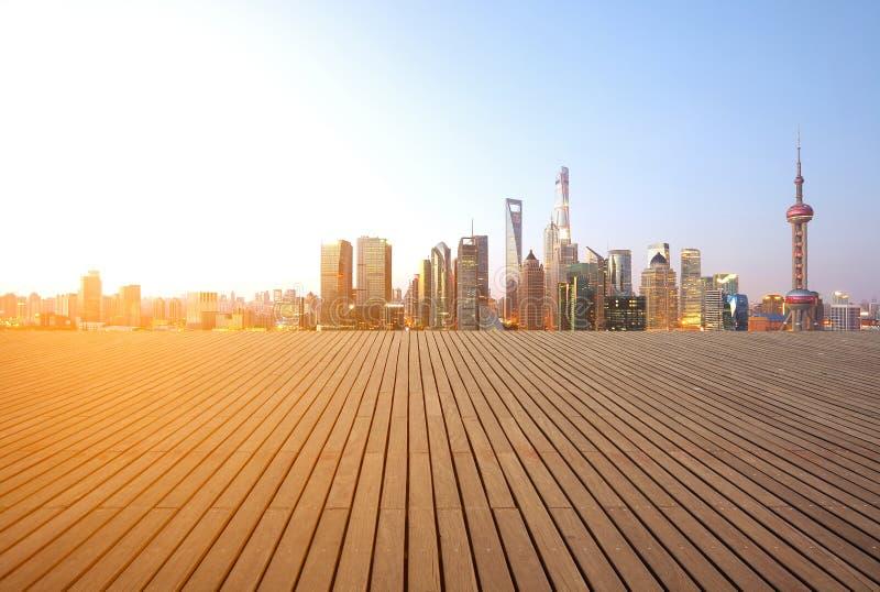 Superficie di legno vuota del pavimento con le costruzioni del punto di riferimento della città fotografia stock libera da diritti