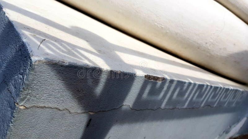 Superficie incrinata dell'angolo della parete dello stucco con il primo piano ornamentale delle ombre di meandro fotografia stock