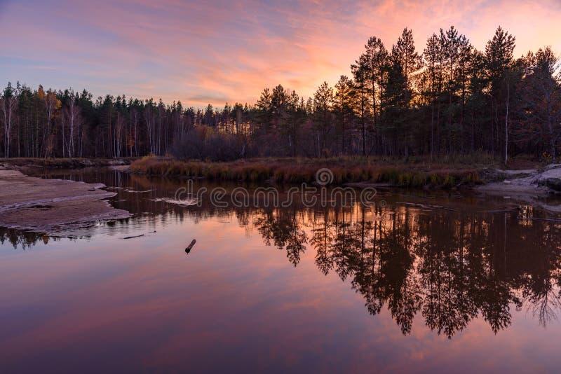 Superficie lisa del agua en el río Reflexión en el agua de árboles, del bosque y de la puesta del sol Rusia fotos de archivo libres de regalías
