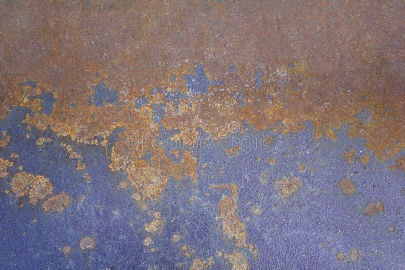 Superficie metallica porpora blu misera del ferro con le macchie arancio marroni della ruggine Struttura approssimativa immagine stock