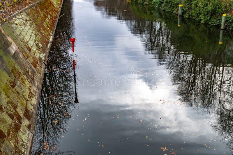 Superficie reflexiva lisa del agua del río de la diversión en Berlin Germany Pared de piedra vieja del terraplén Reflexión borros foto de archivo libre de regalías
