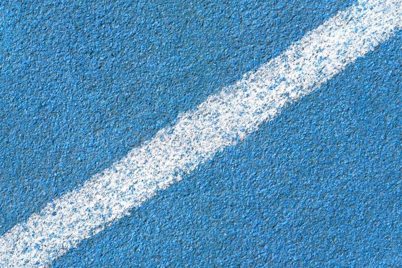 Superficie sintética azul de una pista del estadio del atletismo con la línea diagonal blanca como textura, extracto del fondo imagen de archivo