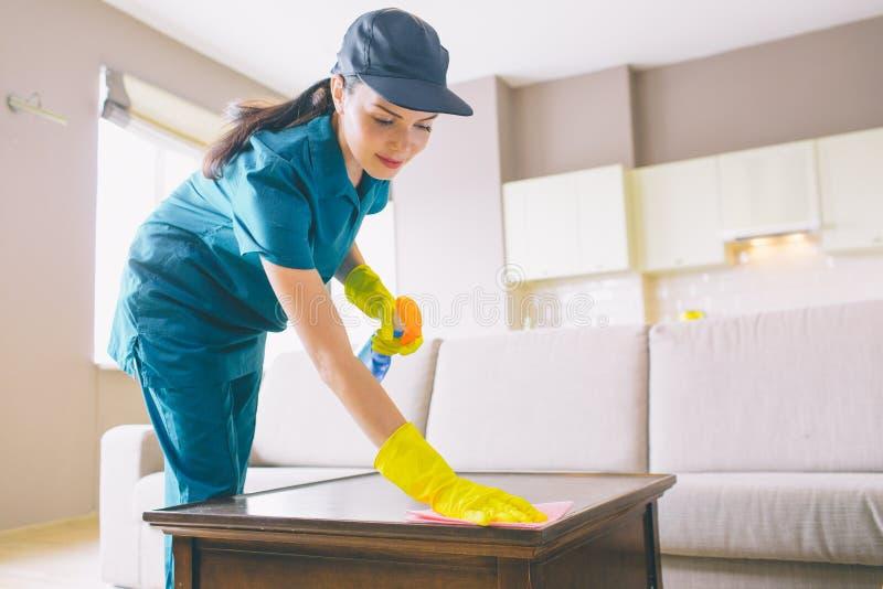 Superficie wahsing del limpiador profesional de la tabla ella utiliza el trapo y el espray La muchacha lo hace cuidadoso fotos de archivo libres de regalías