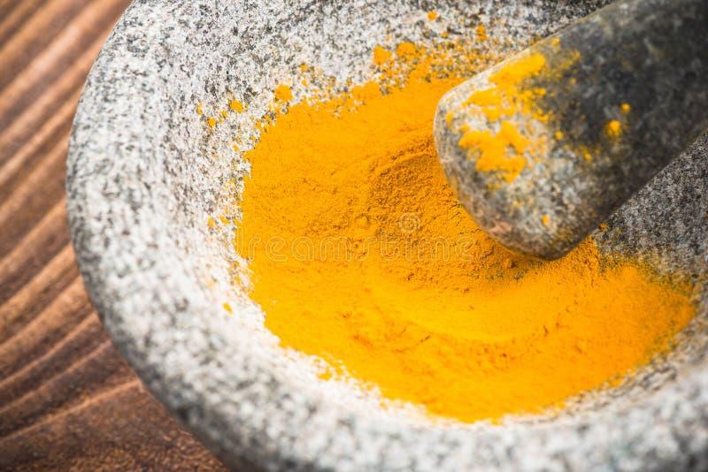 Superfood de poudre de safran des indes en pilon ou mortier de granit image stock