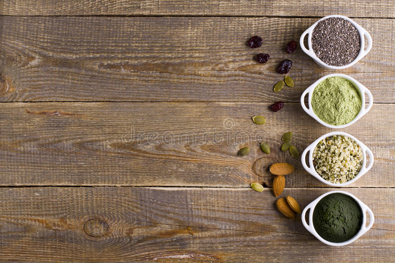 Superfood raw seeds and powder. Body building powders and health food on wooden background. Superfood served in small bowls royalty free stock images