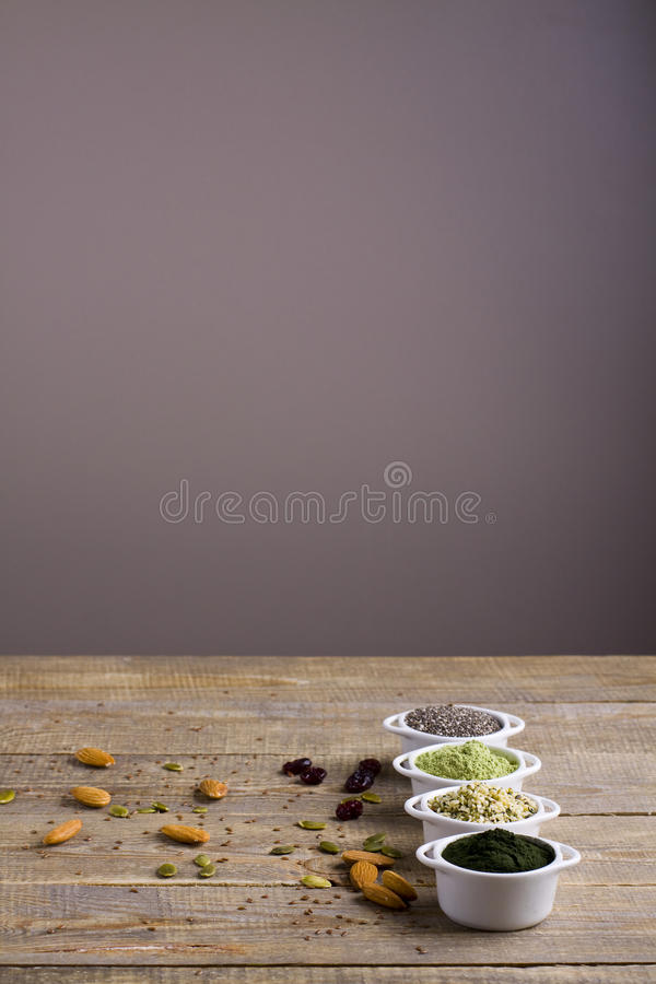Superfood raw seeds and powder. Body building powders and health food on wooden background. Superfood served in small bowls royalty free stock photography