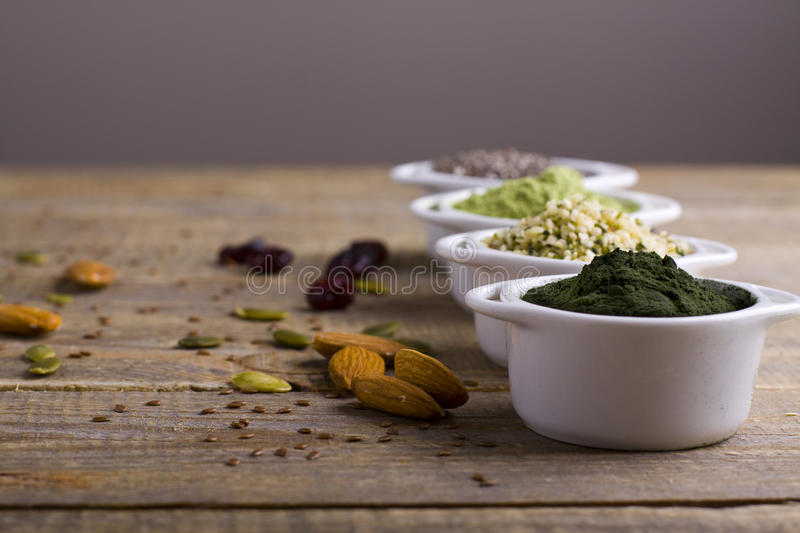 Superfood raw seeds and powder. Body building powders and health food on wooden background. Superfood served in small bowls stock photography