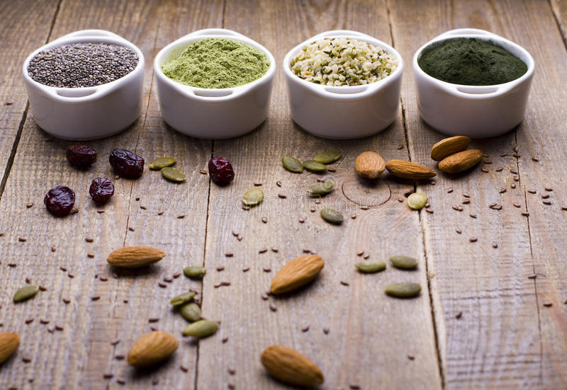 Superfood raw seeds and powder. Body building powders and health food on wooden background. Superfood served in small bowls royalty free stock image