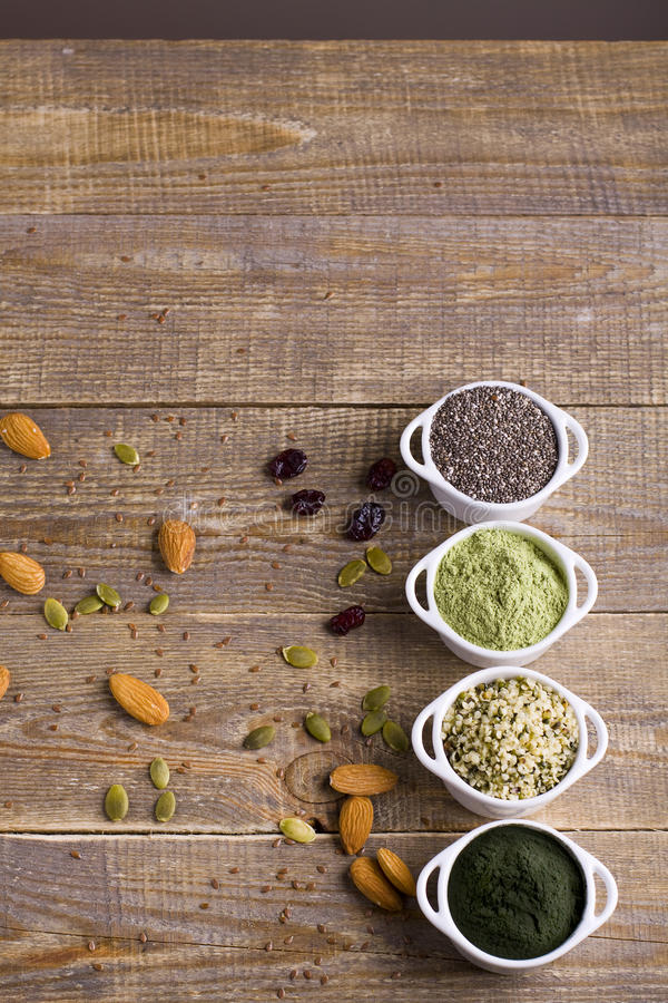 Superfood raw seeds and powder. Body building powders and health food on wooden background. Superfood served in small bowls stock photos