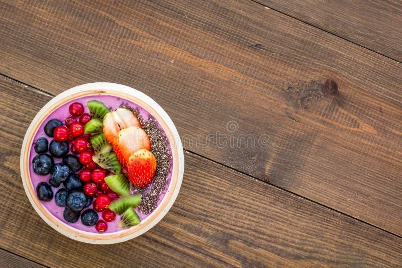 Superfoods Acai-Smoothieschüssel mit frischen Früchten, Beeren, chia Samen auf dunklem hölzernem Draufsichtraum des Hintergrundes lizenzfreie stockfotos