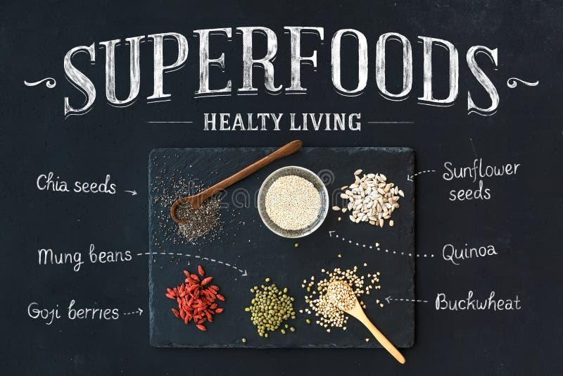 Superfoods on black chalkboard background: goji berries, chia, mung beans, buckwheat, quinoa, sunflower seeds. Top view royalty free stock photo