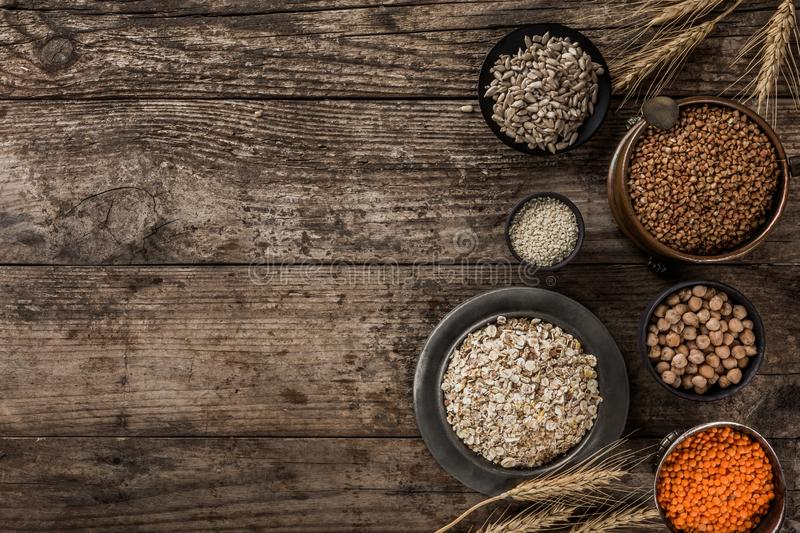 Superfoods and cereals selection in bowls, chickpeas, lentils, buckwheat, oatmeal, flax seeds, sunflower seeds. On rustic wooden background. Healthy food stock image