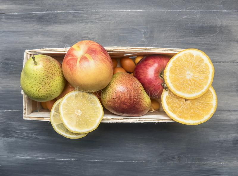 Superfoods and health detox diet food concept variety of fruits in a wooden box kumquat, oranges, pear, lemon, top view royalty free stock photo